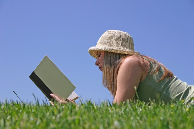 white woman reading book on green grass